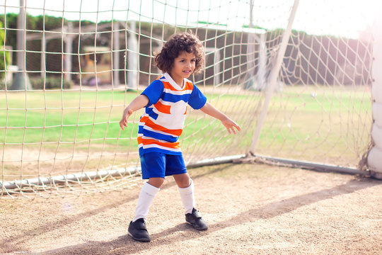 Little boy plays football outdoor. Children and lifestyle concept