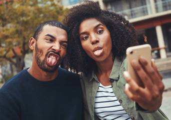Young couple making funny face while taking selfie on smart phone
