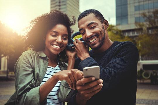 Young couple enjoying music on wireless headphone