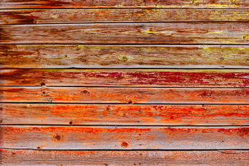 Old Board painted with orange red paint. Worn wood texture, background.