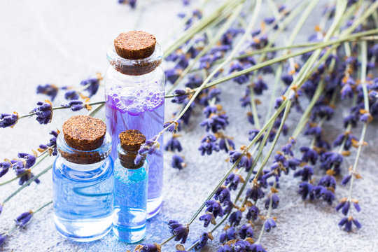Spa and wellness setting with lavender flowers, sea salt, oil in a bottle, aroma candle on wooden white background