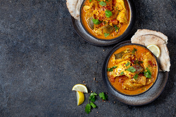 INDIAN FOOD. Traditional KERALA FISH CURRY with naan bread, gray plate, black background