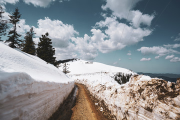 Narrow mountain dirt road has two sides off snow in winter
