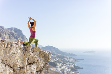 Young Caucasian woman practicing yoga or working out while standing on cliff