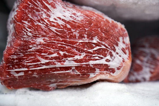 Large pieces of red meat in a freezer with a big quantity of frozen ice and snow