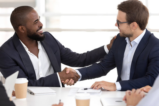 Happy diverse businessmen partners shake hands at meeting negotiations