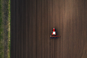 Top view of tractor planting corn seed in field