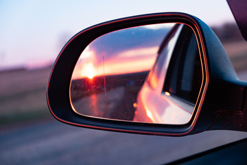 The reflection of the setting sun in the rearview mirror of the car