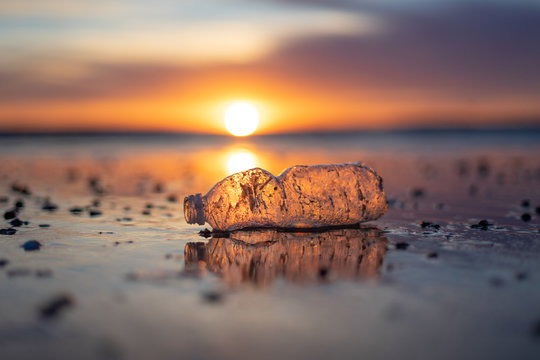 A plastic bottle floating in the sea in a beach with dirty coast