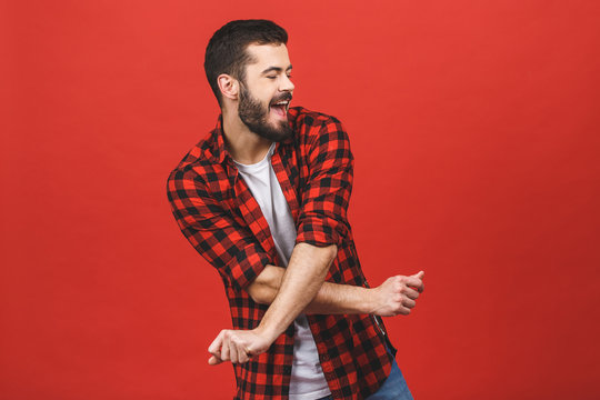 Photo of handsome young man dancing isolated over red wall background.