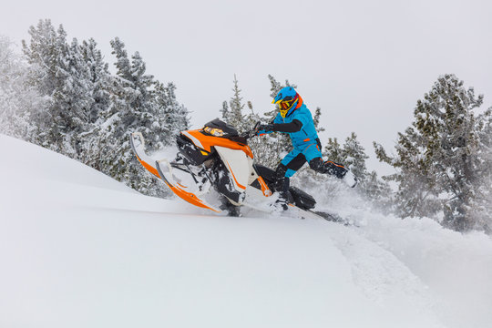 snowmobile before the jump. mystical forest in the mountains with snow-covered cedars. snowmobile jump. bright snowmobile in motion. orange-white bike, beautiful helmet and suit