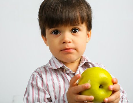 Small caucasian boy with dark hair, big dark eyes, wearing striped shirt is eating big green apple, isolated on white background