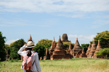 Fototapete - Young woman traveling backpacker with hat, Asian traveler looking Beautiful ancient temples and pagoda, landmark and popular for tourist attractions in Bagan, Myanmar. Asia Travel concept