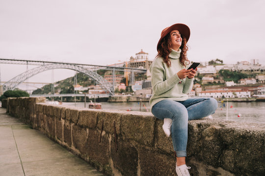 A beautiful young woman traveler is enjoying sightseeing in Porto. She is sitting on a wall near the bridge while laughing using her mobile phone. Lifestyle