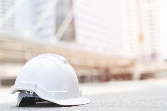 white hard safety wear helmet hat in the project at construction site building on concrete floor on city with sunlight. helmet for workman as engineer or worker. concept safety first.