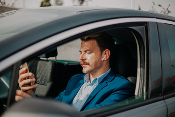 Handsome bearded businessman texting in the phone while driving and using wireless earphones in car
