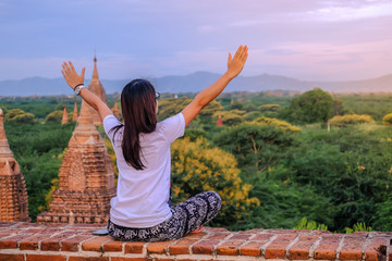 Fototapete - Young happy woman traveling, Asian traveler on Pagoda and looking Beautiful ancient temples, landmark and popular for tourist attractions in Bagan, Myanmar. Asia Travel concept