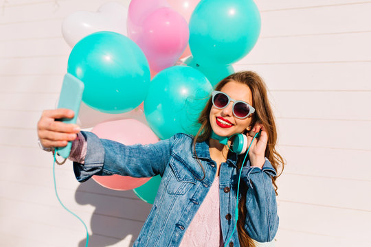 Happy birthday girl with balloons making selfie while listening music and enjoying party. Charming brunette young woman in denim jacket and stylish sunglasses taking photo from event for instagram.