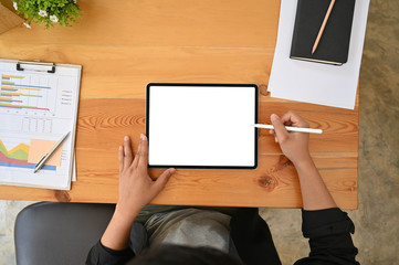 Top view man using digital mockup tablet and pen on wood table with finance business paper.