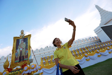 Woman takes a selfie with Thailand's King Maha Vajiralongkorn's picture in the background, near the Grand Palace, ahead of the king's coronation, in Bangkok