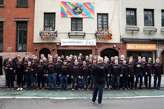 Artistic Director of the San Francisco Gay Men's Chorus Tim Seelig leads the choir while singing on the street in front of the historic gay bar the Stonewall Inn in the Manhattan borough of New York