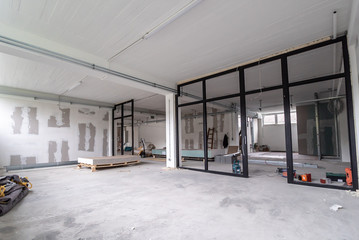 Obraz Interior empty office light room in a new building renovation or under construction. Glass doors and Windows - fototapety do salonu