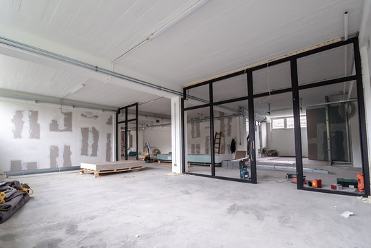 Interior empty office light room in a new building renovation or under construction. Glass doors and Windows