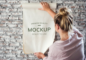 Woman Rolling Out Poster on Brick Wall Mockup