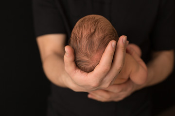 the child's head in the hands of parents. the head of the newborn in the hands of his father. the little head of a newborn