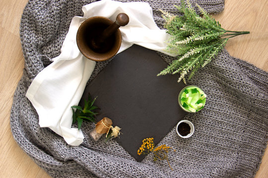 natural slate slab surrounded by herbs, alchemy appliances, potions and ingredients lies on a table. fabric linen and knitted around.  Flat lay with copy space for text.