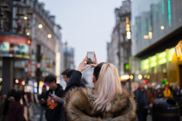 Woman tourist taking pictures of city with her cellphone in blurred background