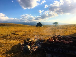 Meat cooking over the fire with a tent in the background, Kazakhstan