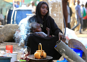 A Sudanese street vendor sells tea as she holds her baby in Khartoum
