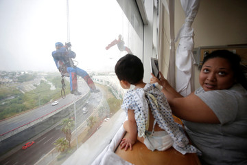 Window-washers, dressed up as superheroes, surprise children as they rappel from the rooftop of a children's hospital in the municipality of Guadalupe