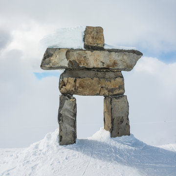 A Stone Inuksuk In The Snow Under A Cloudy Sky With A Snow Covered Mountain In The Background; Whistler, British Columbia, Canada