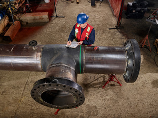 A Tradesman Stands At A Large Pipe And Writes On A Document; Edmonton, Alberta, Canada