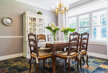 Wooden Dining Table With High-Back Sitting Chairs And White Buffet In The Dining Room With Earth Tone Slate Flooring Inside A Contemporary Cottage Style Home; Quebec, Canada