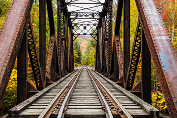 Iron railroad bridge over Sawyer River with trees in autumn colours, White Mountains National Forest; New England, United States of America