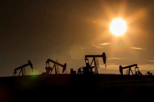 Silhouette of numerous pumpjacks in a field with a glowing sun at sunset on the Alberta Prairies, West of Airdrie; Alberta, Canada