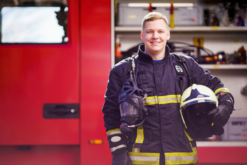 Photo of happy male firefighter with helmet in his hands against background of fire truck