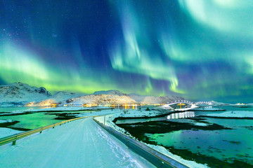 Papiers peints Aurore polaire Aurora Borealis natural phenomenon on Lofoten Islands in Norway, Scandinavia, Europe. Night sky with northern lights over mountains and road reflected in fjord. Night winter landscape with aurora.