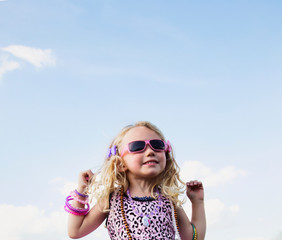 A young girl all dressed up with blond curly hair wearing sunglasses and jewelry standing making cute faces against a blue sky with cloud; Spruce Grove, Alberta, Canada