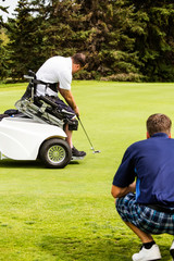 An able bodied golfer teams up with a disabled golfer using a specialized powered golf wheelchair and helps him to line up his putt on a golf green at a golf course; Edmonton, Alberta, Canada