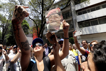 A supporter of Venezuelan opposition leader Juan Guaido holds up a picture of late Venezuela's President Hugo Chavez during a protest outside the Venezuelan embassy in Mexico City
