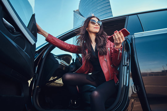 Beautiful smart women is posing in her new car while chatting on mobile phone. She is wearing red leather jacket and sunglasses.