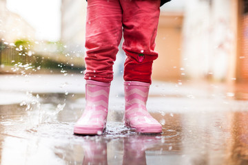 Child standing with pink rubber boots in puddle in rain. Kind steht mit rosa Gummistiefeln in Wasserpfütze im Regen.