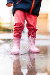 Kind springt mit rosa Gummistiefeln in Wasserpfütze. Child jumping with pink rubber boots over puddle.