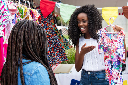 Beautiful african american market vendor presenting clothes to customer