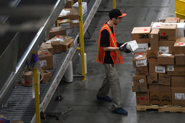 Worker handles a package at the Amazon fulfillment center in Baltimore