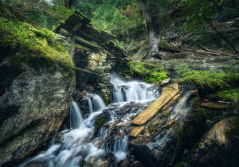 Wall Mural - Stony well in colorful green forest with little waterfall in mountain river at sunset in summer. Landscape with stones in water, building, trees, waterfall and vibrant foliage. Nature. Blurred water